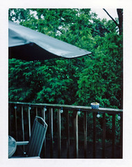 Rainy Day (Brock5604) Tags: wood trees summer green film nature water rain umbrella dark table polaroid lights wooden chair day fuji cloudy outdoor rail drip pot rainy porch land instant dull pouring