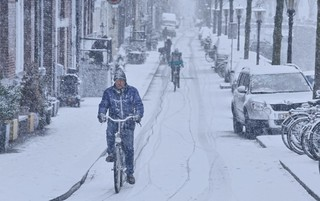 Toiling by bike through a snow blizzard in Amsterdam
