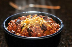 Chili con carne with cheese in a bowl (Holly&Sage) Tags: food cooking horizontal closeup cheese dinner silver lunch stew beans chili beef spice fork nobody bowl vegetable meat steam meal dining cooked foodanddrink chilipepper consoling pintobean colorimage mexicancuisine savoryfood