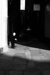 Stranger In The Light (Mudi Chris) Tags: blackandwhite sun sunlight london monochrome contrast strangers streetphotography shade fujifilm x100 fujix100