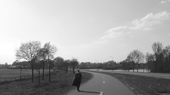 Easter sunday walk (andzwe) Tags: road shadow bw woman dutch vintage blackwhite costume highway zwartwit serene drente drenthe peasant klederdracht dutchlandscape snelweg fietspad staphorst filmisch schiphorst sereen dewetering boerin drenthenetherlands