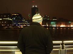 Thames Man (lindscatt) Tags: city winter man cold london hat thames night dark lights back coat nighttime frombehind citylights behind railing riverthames atnight artificiallight wrappedup londonthames londonriver
