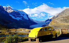 Vintage yellow snowmobile and the Athabasca Glacier (peggyhr) Tags: blue sky white snow canada mountains green yellow clouds glacier alberta bushes jaspernationalpark athabascaglacier peggyhr vintagesnowmobile dsc08440a