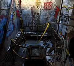ichabod circle T (bobsnikond200) Tags: skull skeleton ichabod graffiti spray paint indoor sunlight natural light ice catwalk railing handrail metal grate rust rusty caution tape ladder valve wheel pipe abandoned blue