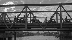 Banjarmasin | Indonesia (Matthew Takata) Tags: bridge blackandwhite monochrome outdoor scooters motorbike traffic travel indonesia banjarmasin street fuji fujifilm fujinon35mmf14xf truss girder beam river