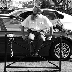Long Time No Shave (ManOn Moon) Tags: flowers portrait white man black look metal work square beard interesting gate long watch guard streetphotography olympus crop sit shave bmw environment rough protection omd 45mmf18 em5