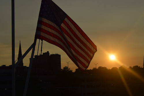 Summer sunset with the United States of America USA flag over the city skyline of New London CT Connecticut USA