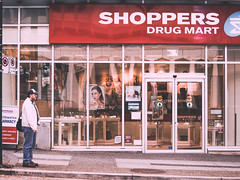 Smoking Drugstore (Jon Cartledge) Tags: golden smooth warm contrast shadow toning dreamy pastel vignetting saturated olympus em5 m zuiko 40150mm f4056 r smoking drugstore canada vancouver bc british columbia shoppers drug mart colour street people robson bus stop smoke color m43 omd thirds four micro lens digital