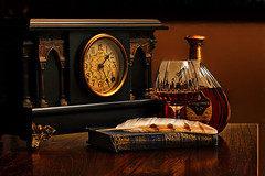 Wrinkles in Time (Goromo) Tags: antique clock mantleclock encyclopedia feather owlfeather stilllife nightshot time cognac memories longexposure
