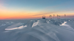 The lonely sled in the icy desert (redfurwolf) Tags: southpole antarctica sled snow drift ice sunset sky clouds orange yellow blue flag outdoor landscape nature redfurwolf rx100m4 sony