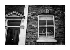 yoga (jrockar) Tags: street door people blackandwhite bw woman house building brick london window yoga wall architecture 35mm lens photography prime mono fuji shot documentary rangefinder snap stretch human madness instant fujifilm moment ordinary decisive ordinarymadness x100s