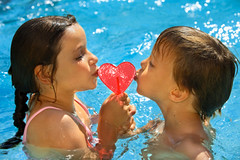 BOY AND GIRL KISSING HEART SHAPED LOLLIPOP IN WATER (shakiradupree) Tags: girls summer portrait love boyfriend boys water pool horizontal closeup outdoors photography togetherness kissing girlfriend couple day child friendship candy heart romance iloveyou lollipop youngcouple twopeople foodanddrink heartshape frontview headandshoulders colorimage childrenonly 67years sweetfood caucasianapparence