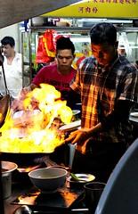 Culinary flame thrower (Peter Denton) Tags: jalanalor bukitbintang streetfood wok flame kualalumpur kl malaysia alfresco ©peterdenton canoneos100d southeastasia candid city capitalcity street cooking stirfry
