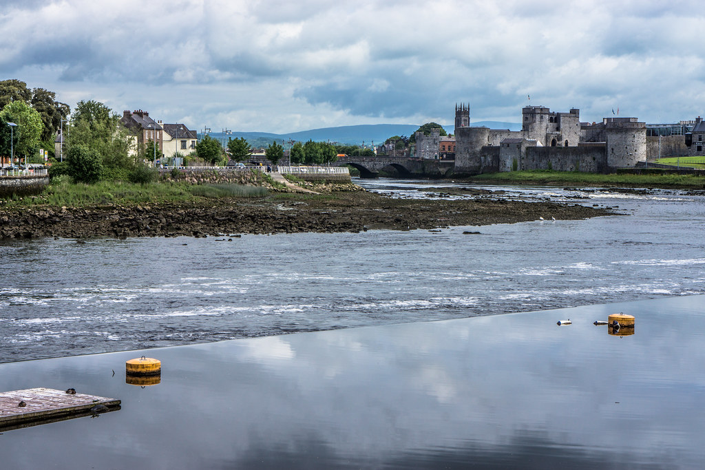 River Shannon Flowing Past King John's Castle In Limerick