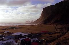 a small town down the cliffs (asketoner) Tags: city autumn houses sea sky mountain fall beach clouds island iceland rocks waves village fingers cliffs vik islande isklandi