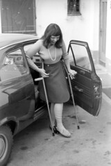 0405b71 07 (ndpa / s. lundeen, archivist) Tags: nick dewolf nickdewolf bw blackwhite photographbynickdewolf film monochrome blackandwhite april 1971 1970s 35mm austria stanton stantonamarlberg austrian people woman maggie crutches oncrutches brokenleg bandaged bandages injury car vehicle automobile gettingoutofacar