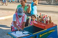 Shaved Ice Treat (fotofrysk) Tags: shavedice raspanaleoneses treat women child ice sauces cart streetvendor hatcentralamericatrip nicaragua leon sigma1750mmf28exdcoxhsm nikond7100 201702030049