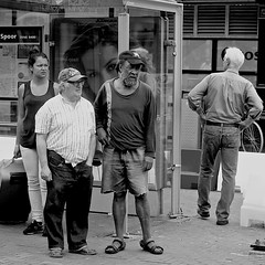 At the tram stop (Akbar Simonse) Tags: people bw pet man holland men blancoynegro netherlands girl monochrome square beard glasses zwartwit sandals candid nederland streetphotography denhaag bn jeans cap shorts spectacles thehague bushalte bril tramstop sandalen baard vierkant tramhalte lahaye sgravenhage agga straatfotografie hereyes