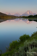 Sunrise illuminates the Grand Tetons as seen from Oxbow Bend