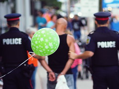 Balloon and Handcuffs (creditflats) Tags: street blue party ontario pen canon lens gun candid balloon jazz blues police custody olympus crime cop mississauga shuffle legacy cuffs arrested arrest 135mm handcuff f35 portcredit ep5 southsideshuffle apprehend