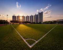Seven Pillars (Scintt) Tags: travel homes light sunset sky urban panorama sun sports field grass lines architecture modern club clouds buildings court private lens landscape living football healthy singapore track apartments glow play exercise natural bright stadium soccer dramatic surreal running structure condo flare housing pitch sunburst burst jogging exploration hdb complex epic parc stitched starburst estates clementi scintillation clementistadium theparccondo scintt