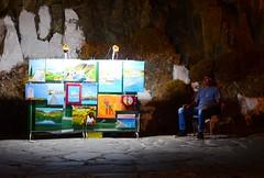 Selling paintings (kutruvis nick) Tags: man art rock night island greek person lights nikon sitting colours village paintings ikaria hellas greece nik selling seller stoneroad armenistis d5100 kutruvis