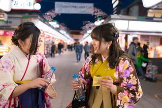 Young women in Hakama walking in traditional shopping street at night