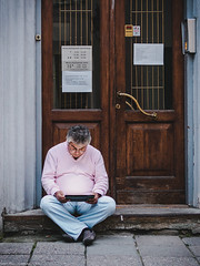 The iPad-Man (samipaju) Tags: street door man tallinn estonia sitting candid doorway tablet focused filmgrain slouch concentrated ipad hunched hunkered