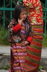 bhutan faces- 53 (cam17) Tags: bhutan dressedup formalwear kira nationalcostume nationaldress wonju fingerinmouth thimputsechu thimpufestival facesofbhutan bhutanfaces bhutanesefaces innationaldress bhutanesecostume bhutanesegarb kiraskirt wonjublouse brightredcuffs kiraandwonju