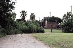 Jackson Barracks, fenced off from the Lower 9th Ward (pop archaeologist) Tags: film fence weeds gate neworleans nikonn90 jacksonbarracks lower9thward 281053545 svema125 neworleansborder