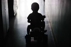 Little Man, Little Machine (N A Y E E M) Tags: umar kalam son toy bike light silhouette corridor 1stfloor home afternoon rabiarahmanlane chittagong bangladesh availablelight indoors naturallight lulu