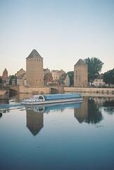 Drifting under bridges (Alejandro Melero Carrillo) Tags: france estrasburgo strasbourg film 35mm río river boat barco towers torres city ciudad reflejo reflection