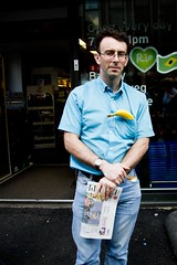 Is That A Banana In Your Pocket Or Are You Just Pleased To See Me? (Leanne Boulton (Busy week, catching up soon)) Tags: life lighting street city blue light shadow summer portrait people urban food sunlight man detail male eye texture face weather yellow shop shirt fruit modern standing landscape fun photography living store aperture focus funny colorful humorous natural humanity outdoor expression candid streetphotography overcast social scene humour banana jeans doorway human shade portraiture denim contact colourful pocket unhappy depth tone facial bulge diffuse humancondition candidstreetphotography