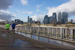 Thames path (Spannarama) Tags: uk reflection men london overgrown thames skyline clouds buildings river puddle jetty running runners blueskies canarywharf railings offices thamespath