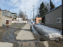 Meltwater courses down an alleyway. (Tim Kiser) Tags: 2015 20150313 highway10 img8687 jamesstreet ludington ludingtonmichigan ludingtonlandscape march march2015 masoncounty masoncountymichigan michigan michiganlandscape route10 southjamesstreet us10 ushighway10 usroute10 alley alleylandscape backalley buildings conifers deliverytruck dirtysnow distanttruck electriclines electricpoles garage garagedoor landscape meltingsnow meltwater mud northmichigan northernlowerpeninsula northernmichigan northwesternlowerpeninsula overheadelectriclines overheadpowerlines partlycloudy paved pavement powerlines runoff siding snowmelt snowylandscape telephonepoles urbanlandscape urbanrunoff utilitypoles view westmichigan westernlowerpeninsula westernmichigan wetpavement windows winterlandscape unitedstates