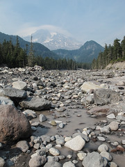 Distant Mount Rainier and the gray waters of the Nisqually River, during a condition of wildfire smoke. (Tim Kiser) Tags: 2015 20150826 august august2015 img2322 longmire longmirearea mountrainiernationalpark mountrainiernationalparklandscape mountrainierlandscape nisquallyriver nisquallyriverlandscape piercecounty piercecountywashington washington washingtonlandscape washingtonstate washingtonstatelandscape boulders coniferforest coniferousforest conifers diffusesunlight distantmountains forestfiresmoke glacialflour glacialriver grayriver graywater greyriver greywater haze hazylandscape landscape mountainlandscape mountainouslandscape mountaintopclouds nationalpark nationalparklandscape park riverboulders riverlandscape riverrocks riverbed riverbedboulders riverbedlandscape riverbedrocks rockflour rocks rockyriver rockyriverbed rockystream rockystreambed smoke smokylandscape streamlandscape suspendedsediment suspendedsediments turbidwater turbidity view westwashington westernwashington wildfirelandscape wildfiresmoke packwood unitedstates