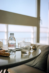Rehydrate and Reload (hjl) Tags: ocean pink blue sea france color beach cup water glass sunglasses table nice cotedazur kodak bokeh pastel balcony rangefinder bottledwater 35mmfilm evian canonetql17 filmphotography portra400 filmrolls