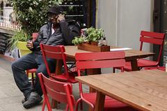 Black and red (tan.ja1212) Tags: köln streetfotografie mütze kopfbedeckung street augen cologne stühle strase tisch telefonieren mann rot red schwarz black man chair table