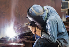 Worker with protective mask welding metal (Bugphai ;-)) Tags: light man industry metal work fire construction industrial factory mask steel welding labor smoke helmet working arc engineering structure gas safety equipment gloves workshop repair technical heat metalwork workplace production worker build laborer craftsman job spark protection making connect assembly fabricate welded skill manufacture welder manufacturing industrialworker builtstructure manualworker protectiveworkwear