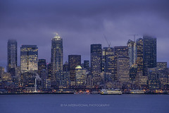 Moody (TIA International Photography) Tags: seattle skyline downtown elliottbay cityscape city waterfront skyscraper illumination buildings cbd ferry ferris wheel evening fog foggy cloudy misty urban landscape washington pugetsound pacificnorthwest cloud cover conceal lights tosinarasi tia ©tiainternationalphotography wsdot transportation reflection