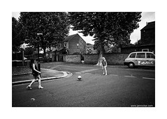 the football craze 1 (jrockar) Tags: road street city uk girls england people urban blackandwhite bw 3 holland london girl kids canon ball children photography mono football mood child play shot kick mark candid fifa cab taxi iii documentary snap human madness instant l 5d worldcup moment craze ef f4 1740 mk ordinary decisive 2014 f4l ordinarymadness
