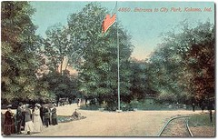 Entrance to City Park, Kokomo, Indiana (Hoosier Recollections) Tags: people woman usa man color men history walking clothing women parks bridges indiana streetscene flags transportation pedestrians railroads kokomo howardcounty hoosierrecollections