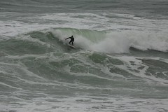Surfing a Building Wave Winter Muriwai New Zealand (eriagn) Tags: sea newzealand weather sport swimming photography coast marine surf waves weekend surfer floating overcast auckland foam surfboard northisland surfers recreation tasmansea westcoast dull leaping wetsuit hightide drizzle competent seaspray flatrock muriwai surging rockplatform foamingsea eriagn ngairelawson ngairehart