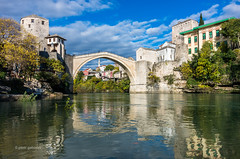 The Old Bridge (pietkagab) Tags: mostar bosniaandherzegovina bosnia bosnian river neretva oldtown oldbridge reflections buildings ottoman architecture mosque muslim autumn autumnal daylight balkans balkanpeninsula pietkagab photography pentax piotrgaborek pentaxk5ii travel trip tourism adventure exploring bluesky clouds medieval unesco