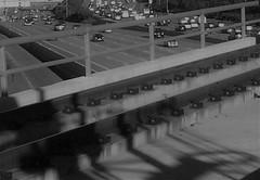 Solid Yet Fluid (Rand Luv'n Life) Tags: odc our daily challenge concret freeway automobile comuter san diego california bridge fence rail tracks shadows rush hour monochrome blackandwhite outdoor cars traffic pov