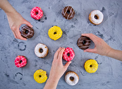 Hands of people taking doughnut on a dark background (♥Oxygen♥) Tags: doughnut day casual people desk group meeting staff part indoors man hands grabbing cool hungry photo junkfood take many icing white sweet overhead fattening view top donuts yellow breakfast orange chocolate iced pink round frosting colorful blue cake glazed various assorted pastry flavors baked food fast plate vintage concrete gray