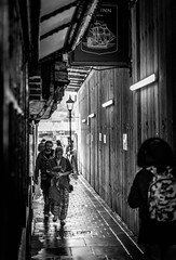 Downcast (Rookie Phil) Tags: exeter outdoor alleyway devon pubsign streetlight street bw monochrome d750 nikond750 people perspective daytime boardedup wetpavement downcast backlit offcathedralclose