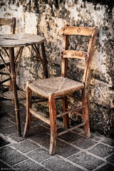 Cretan Comfort (Cirrusgazer) Tags: outside greek wooden cafe chair empty character traditional used greece crete worn weathered wicker comfy absence kafenion