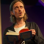 Mackenzie Crook reading on stage at the Edinburgh International Book Festival