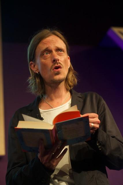 Mackenzie Crook reading on stage at the Edinburgh International Book Festival